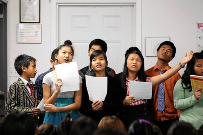 Ruth Iang, left, 13, Sui Me Zi, center, 13, Ngun Hnem Iang, right, 10, all of Elkridge sing during the children's service at Cornerstone Church in Columbia.