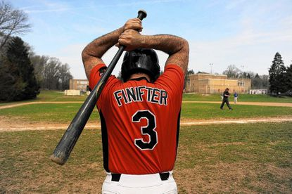 John Finifter stretches before taking the plate during opening day of the Over 40 Baseball League on Sunday, April 13.
