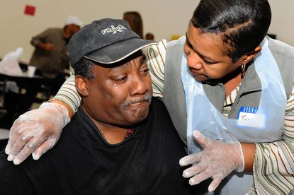 Anthony Clark, 57, is embraced by volunteer Ingrid Collazo, as he sheds tears of appreciation at Thanksgiving dinner at Booker T. Washington Middle School.