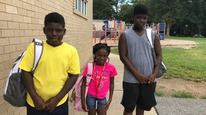 Javen Perry, 11 (left), Kelis Perry, 9, (middle) and Jeremy Perry, 13 (right) pose wearing their new backpacks from the United Way event at Cradlerock Elementary School on Wednesday Aug. 22.