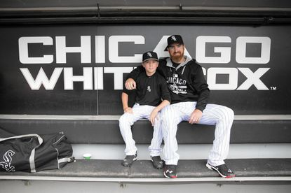 Chicago White Sox designated hitter Adam LaRoche (25) sits with his son Drake, 13, in the White Sox dugout at U.S. Cellular Field before a game against the Houston Astros on June 8, 2015 in Chicago.