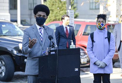 Mayor Brandon M. Scott provides an update on Baltimore's response to the COVID-19 pandemic along with Baltimore City Health Commissioner Dr. Letitia Dzirasa, right, in front of City Hall.