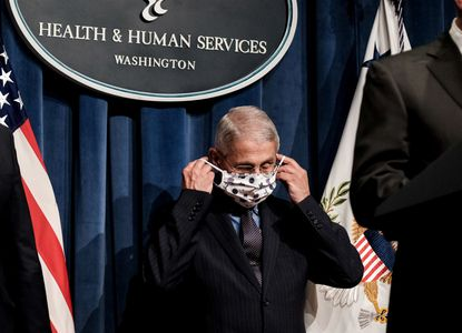 Dr. Anthony Fauci, director of the National Institute of Allergy and Infectious Diseases, puts on a face mask during a coronavirus task force briefing in Washington on June 26, 2020.