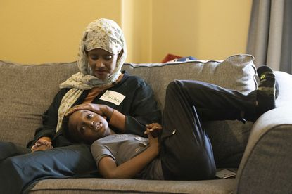 Shukri Olow, left, a Muslim woman who is running for a council seat in Kent, Washington., snuggles with her son. Young adult Muslim Americans, who grew up amid the aftershocks of the Sept. 11, 2001, terrorist attacks, came of age in a world not necessarily attuned to their interests, happiness or well-being. Olow says the aftermath of the attacks has helped motivate her to become a community organizer and to run for office in Washington state. (AP Photo/Karen Ducey)