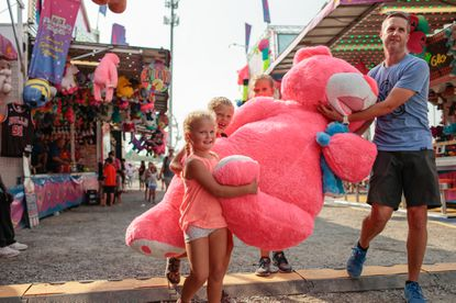 Brian Pietryka, of Fulton, helps his daughters, from left, Maeve, 4, Sloane, 7, and Blythe, 9, carry the giant teddy bear they won at the Howard County Fair.