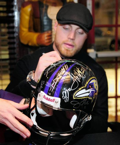 Baltimore Ravens Paul Kruger adds his to the autographs on a Ravens helmet at the Dark Horse Saloon in Bel Air Friday night.