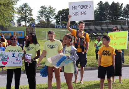 Outside River Hill High School, people protest a plan to redraw boundaries in Howard County to bolster diversity.