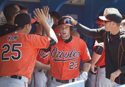 Baltimore Orioles' Joey Rickard is congratulated in the dugout after hitting a home run in the fourth inning of a baseball game against the Toronto Blue Jays in Toronto, Saturday, June 11, 2016.