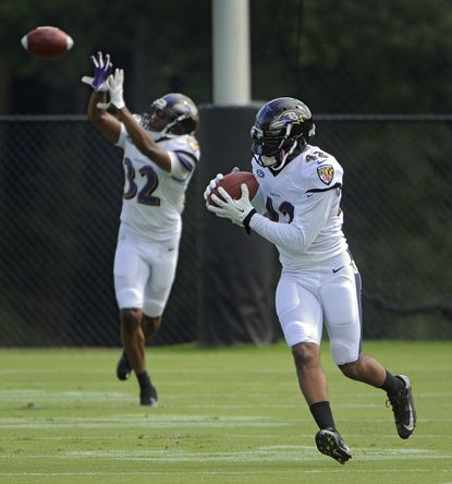 Ravens cornerback Deji Olatoye, left, follows safety Dominique Franks during a training camp practice at the Under Armour Performance Center.