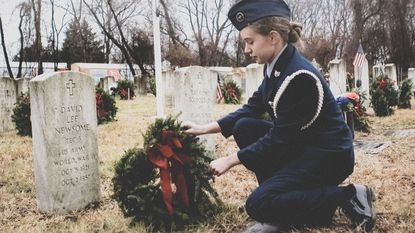 A member of the Harford Composite Squadron of the Civil Air Patrol at Aberdeen Proving Ground lays a wreath at the grave of a veteran Saturday at Angel Hill Cemetery in Havre de Grace as part of Wreaths Across America.