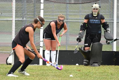 Junior Kirby Henneman, center, positions herself next to senior goalie Payton Steele tries as she waits for a teammate to send the ball towards the goal during Westminster's field hockey team practice at the school on Tuesday, August 27.