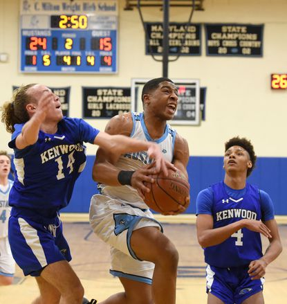Kenwood's Anthony Ortiz reaches out to try for the block as C. Milton Wright's Bryan Stiemke goes strong to the basket during Tuesday night's playoff game at C. Milton Wright.