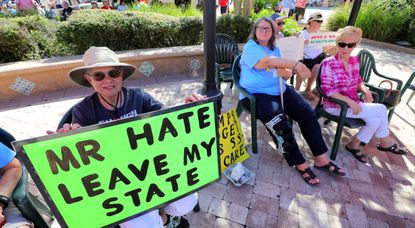 Proponents of the impeachment of President Donald Trump hold signs outside the Sharon L. Morse Performing Arts Center, before President Trump's appearance, in The Villages, Fla. on Oct. 3.