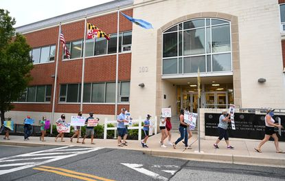 People march in front of the Harford County Public Schools office building last month during a protest by local parents, students and teachers, to reopen the school system to in-person learning in the fall.
