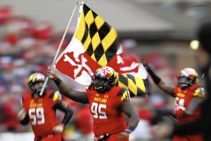 Maryland defensive lineman Azubuike Ukandu (95) carries a Maryland flag as he runs onto the field with teammates before an NCAA college football game against Wisconsin, Saturday, Nov. 7, 2015, in College Park, Md. (AP Photo/Patrick Semansky)