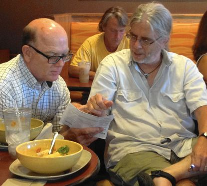 Tom Grapes, left, asks his friend, Tim Lawrence, about an especially difficult puzzle cache that Lawrence made, during a C3F geocaching meeting at Panera Bread, in Eldersburg, June 16._- Original Credit: Natalie Eastwood/Staff photo