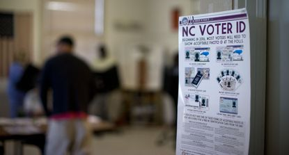 Voter ID rules are posted at the door of the Alamance Fire Station on March 15 in Greensboro, N.C.
