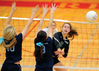 Mount de Sales' Emily Smith, left, and Lynn Walsh, right, faced St. Paul's hitter Kendall Burdette in the IAAM A Conference volleyball championship match last year. Smith returned this season for the Sailors who lost to Spalding in four sets Friday night.