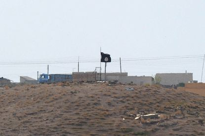 An Islamic State (ISIS) black flag flies near the Syrian town of Kobani, as seen from the Turkish-Syrian border.