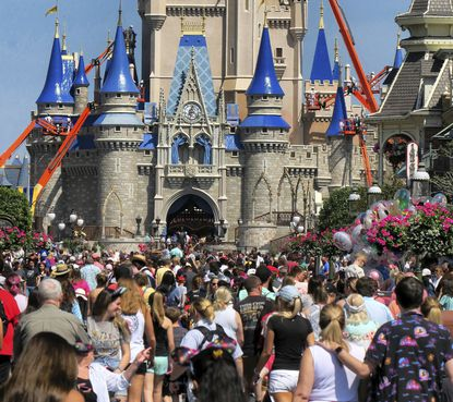 FILE - In this March 12, 2020, file photo, a crowd is shown along Main Street USA in front of Cinderella Castle in the Magic Kingdom at Walt Disney World.