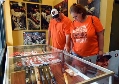 Baltimore, MD -- 9/28/15 -- Tom and Robyn Harrington of Bel Air look at the game used Oriole bats in the Orioles Authentics store on Eutaw Street.