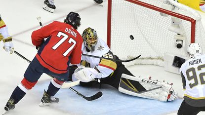 Capitals right wing T.J. Oshie (77) scores around the defense of Vegas Golden Knights goaltender Marc-Andre Fleury (29) in the first period during Game 4 of the Stanley Cup Final on Monday.