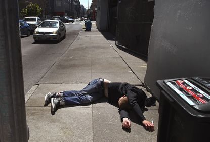 In this April 26, 2018, file photo, a man lies on the sidewalk beside a recyclable trash bin in San Francisco, California. A record number of people died of drug overdoses in San Francisco last year, a crisis fueled by the powerful painkiller fentanyl. (AP Photo/Ben Margot, File)