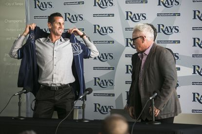 Grant Balfour pulls on a Rays jersey as Tampa Bay manager Joe Maddon looks on during a news conference Thursday announcing Balfour's signing.
