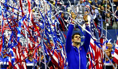 Novak Djokovic celebrates with the winner's trophy after defeating Roger Federer during their Men's Singles Final match on Sunday.