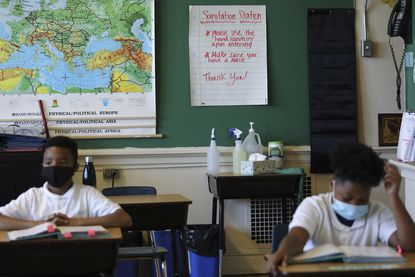 Students at Jayne Royal's 5th grade class, wear masks and have a table with disinfectants and hand sanitizer near the door at St. Malachy School in the west side of Chicago, Wednesday Oct., 7, 2020.