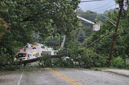 BGE crews work to replace power lines after a tree fell, taking out the lines and blocking Frederick Road near Dutton Avenue in Catonsville Sunday morning.