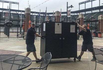 Workers move voting equipment into Oriole Park at Camden Yards to set up for the start of early voting Monday in Maryland
