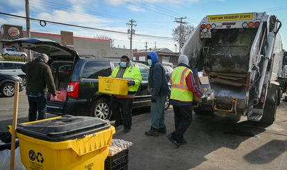 Baltimore Department of Public Works employees help move recyclables from a resident's car to a sanitation truck at the Sisson Street drop-off facility in January just days before curbside recycling pickups resumed after being shut down due to the COVID-19 pandemic. (Jerry Jackson/Baltimore Sun).