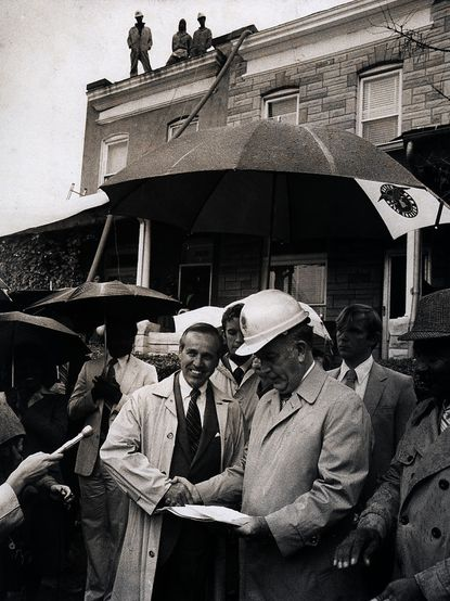 Bernard C. Trueschler was BGE's CEO from 1980 to 1987. Here, Baltimore Mayor William D. Schaefer, in hard hat, accepts a $52,000 check from Mr. Trueschler to help fund a weatherization program to insulate about 100 homes in West Baltimore. The business grant was part of the $500,000 Blue Chip-in program, in which businesses sponsor financially strapped city agency projects. William H. Mortimer/Baltimore Sun 1981