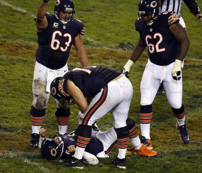 Jay Cutler is helped by teammates after being hit during the second quarter Sunday.