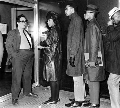 In 1963, a man blocks the entrance to the Northwood Theater where some 150 members of the Civic Interest Group demonstrated last night. All were arrested and charged with trespassing and disorderly conduct during the protest against segregation at the theater.