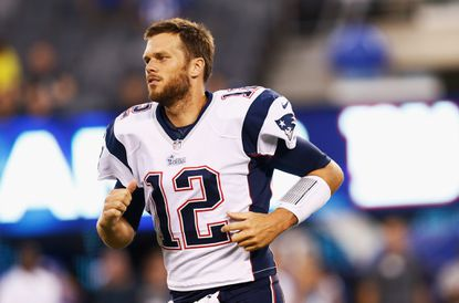 Patriots QB Tom Brady runs onto the field before the preseason game against the Giants.