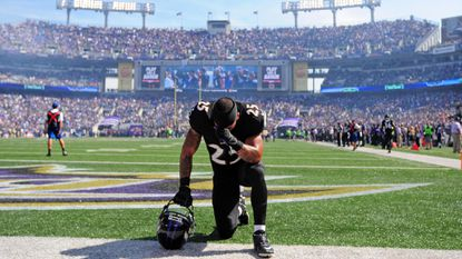 Ravens cornerback Asa Jackson prays on the field before the team's game against the Panthers at M&T Bank Stadium on Sept. 28.