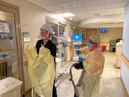 Bree Weyer and Hannah Storch, nurses in the intensive care unit at University of Maryland Upper Chesapeake Medical Center, put on protective equipment.