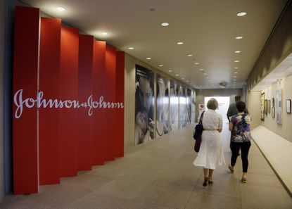 FILE - In this July 30, 2013, file photo, people walk along a corridor at the headquarters of Johnson & Johnson in New Brunswick, N.J. A Philadelphia jury has ruled that Johnson & Johnson and Janssen Pharmaceuticals must pay $8 billion in punitive damages over an antipsychotic drug linked to the abnormal growth of female breast tissue in boys. A law firm for the plaintiff released a statement Tuesday, Oct. 8, 2019, saying the companies used an organized scheme to make billions of dollars while illegally marketing and promoting the drug called Risperdal. (AP Photo/Mel Evans, File)