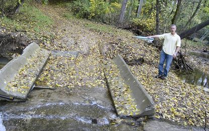 Mountain biker David Wassel points to a bridge on a DPW fire road that bikers said has caused erosion.