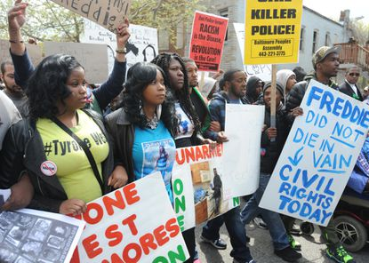 Tawanda Jones, sister of Tyrone West (second from left), who died while in police custody in 2013, takes part in the march to protest the death of Freddie Gray who was in police custody.