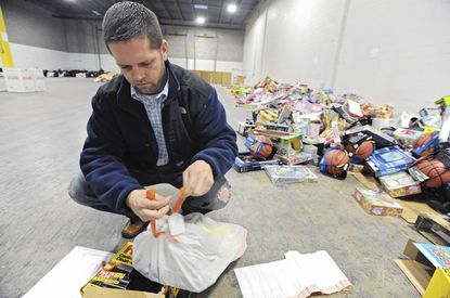 Volunteer Tom Sullivan, of Canton, bags toys for a needy family at the Toys for Tots warehouse.