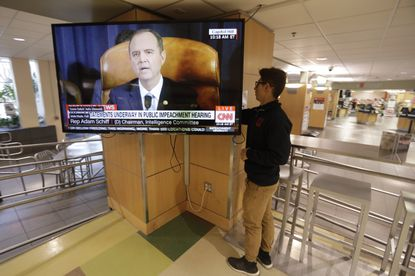 University of Utah student Suyog Shrestha turns on a TV in the student union on the campus in Salt Lake City as Rep. Adam Schiff, the Democratic chairman of the House Intelligence Committee, makes his opening remarks Wednesday, Nov. 13, 2019, as the House panel launched the first public hearing of Donald Trump's impeachment investigation. (AP Photo/Rick Bowmer)