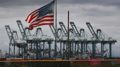 U.S. US flag flies over shipping cranes and containers in Long Beach, California. The skyrocketing U.S. trade deficit last year hit the highest level in a decade, a major setback for President Donald Trump's global trade offensive.
