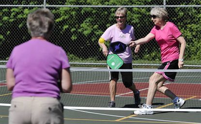 If it's Tuesday morning at the Churchville Rec Center, it must be pickleball. Left to right, Rene Doyle, Forest Hill, waits as opponents Maureen Mills, Bel, Air and Sue Parker, Bel Air, move to return the ball.