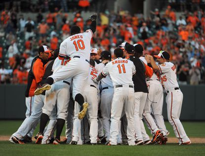 The Orioles celebrate their 14-innings victory over the Rays on Thursday.