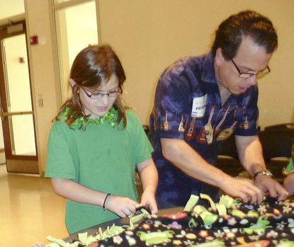 Douglas Stagnaro and St. Louis School third-grader Katie Ryder put the finishing touches on a blanket for the Linus Project, a a nonprofit providing warmth and comfort to seriously ill or traumatized children
