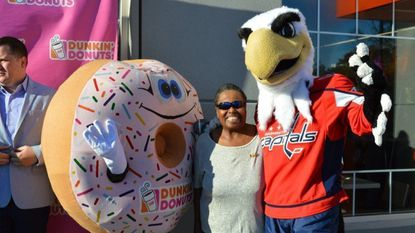 Dee Slater poses with the Dunkin' mascot and the Washignton Capitals hockey team mascot.