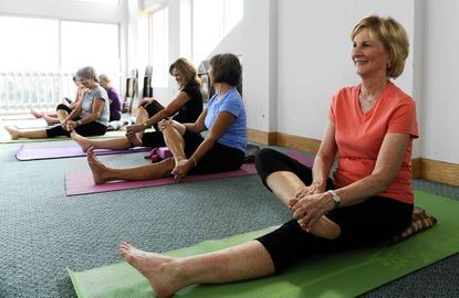 Jaymee Farinacci, right, and others do a stretch at the Kingsville Recreation Council's yoga class at the Mt. Vista Regional Park.